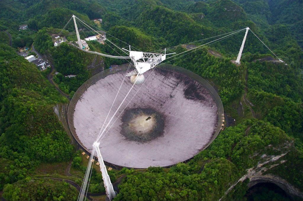 Photo aérienne de l'antenne géante du radiotélescope d'Arecibo sur l'île de Porto Rico dans les Antilles. Elle se trouve au milieu de la forêt et le cliché est pris de jour.