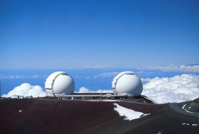 Photo des deux télescopes jumeaux Keck I et II par beau temps, sur le mont Mauna Kea de l'île d'Hawaï. Il surplombent les nuages.