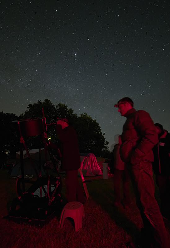 Observateurs en groupe autour d'un télescope Dobson