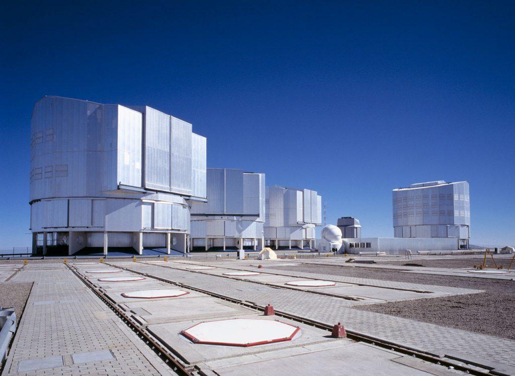 Photo montrant les six dômes composant le VLT, de gauche à droite: ANTU, KUEYEN et MELIPAL, les trois premiers télescopes principaux, un des quatre télescopes auxiliaire AT1, le VLT Survey Telescope et le dernier des quatre télescopes principaux YEPUN.