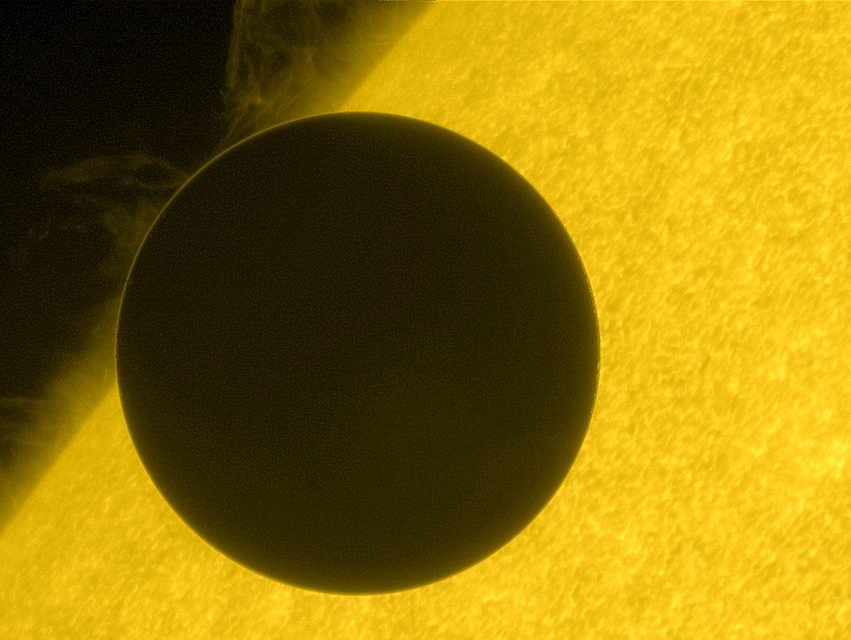 La planète Vénus (sombre) est vue entière en train de passer devant le Soleil (jaune), que l'on ne voit pas en entier. Image de la mission Jaxa/Nasa Hinode.