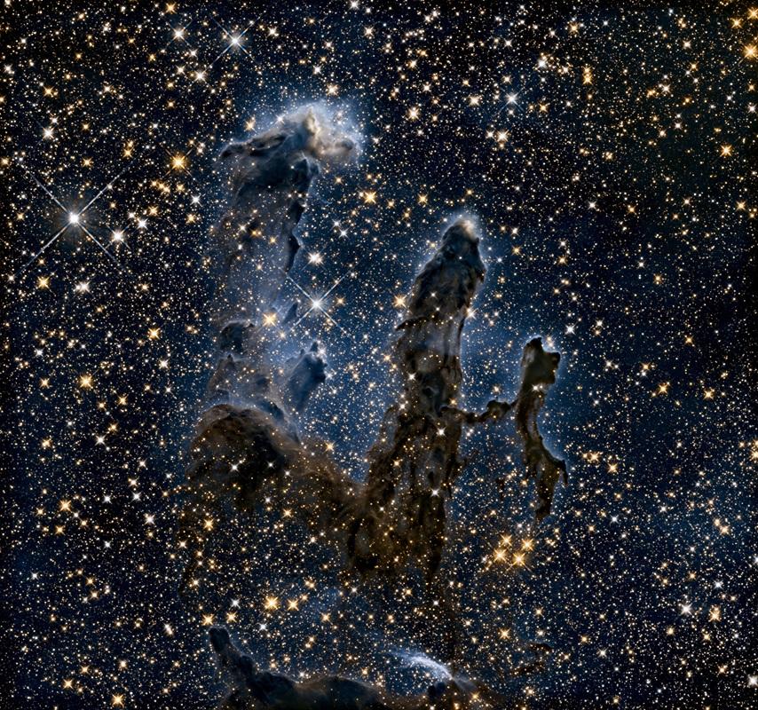 La nébuleuse de l'Aigle vue par Hubble en avril 2015. La nébuleuse, gaz et poussières gris foncé, sont visibles devant un fonds très étoilé.