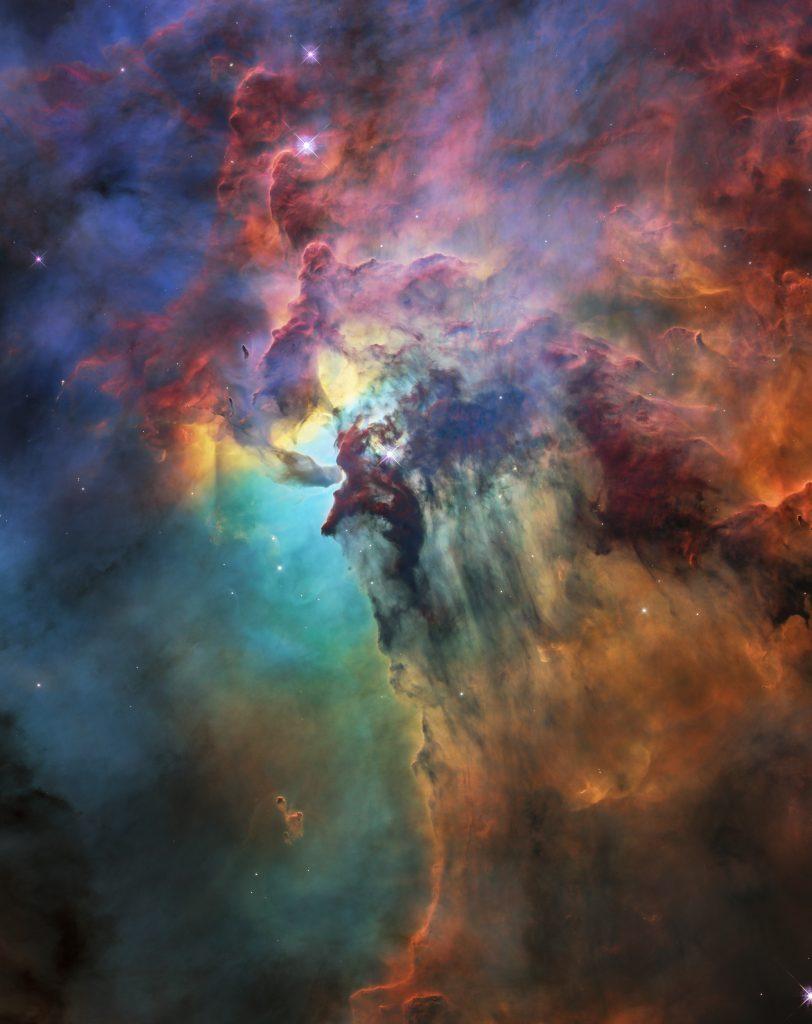 Impressionante image de la nébuleuse du Lagon prise par Hubble pour son 28e anniversaire. Couleurs : turquoise, rouge et noir.