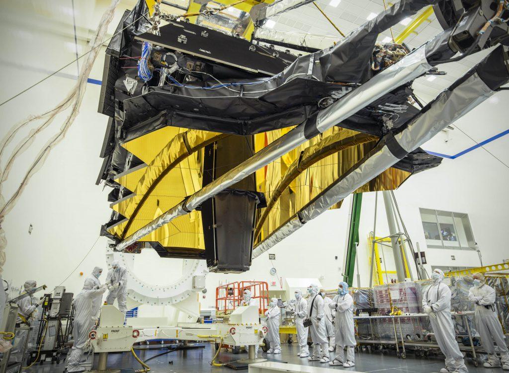 Le JWST en salle blanche en Californie. Il est suspendu en l'air au-dessus des ingénieurs en blouse blanche qui participent à son test et à son intégration.