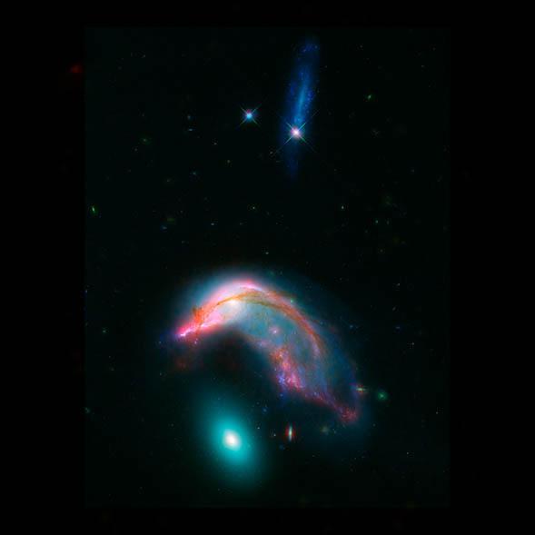 """Image combinée de Spitzer et Hubble, de deux galaxies en interaction: NGC 2336 """"le pingouin"""" et NGC 2937 """"l'oeuf"""". L'oeuf en bas de l'image dans les tons bleu brillant, est surplombé par un pingouin rose et turquoise, tordu comme s'il le couvait."""