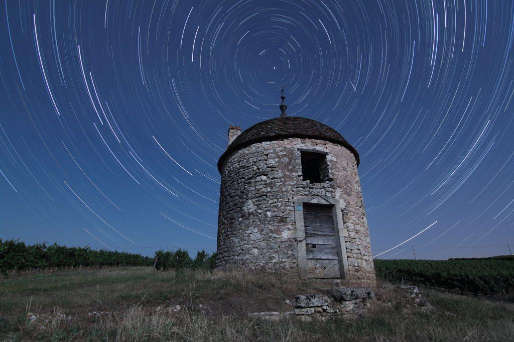 Photo montrant le mouvement apparent du ciel dû à la rotation de la Terre. Les étoiles semblent tourner autour de l'étoile Polaire au fil des heures.