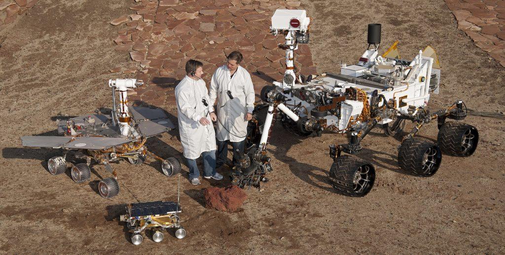 Photo couleur des maquettes en taille réelle des trois rovers Sojourner (premier plan), Opportunity (à gauche) et Curiosity (à droite) aux côtés de deux ingénieurs du Jet Propulsion Laboratory de la Nasa (Californie) où ils ont été développés.