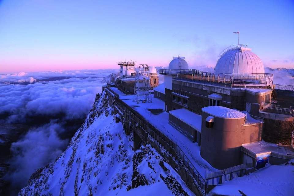 Observatoire du Pic du Midi à l'aube, la neige est dans les tons violets.