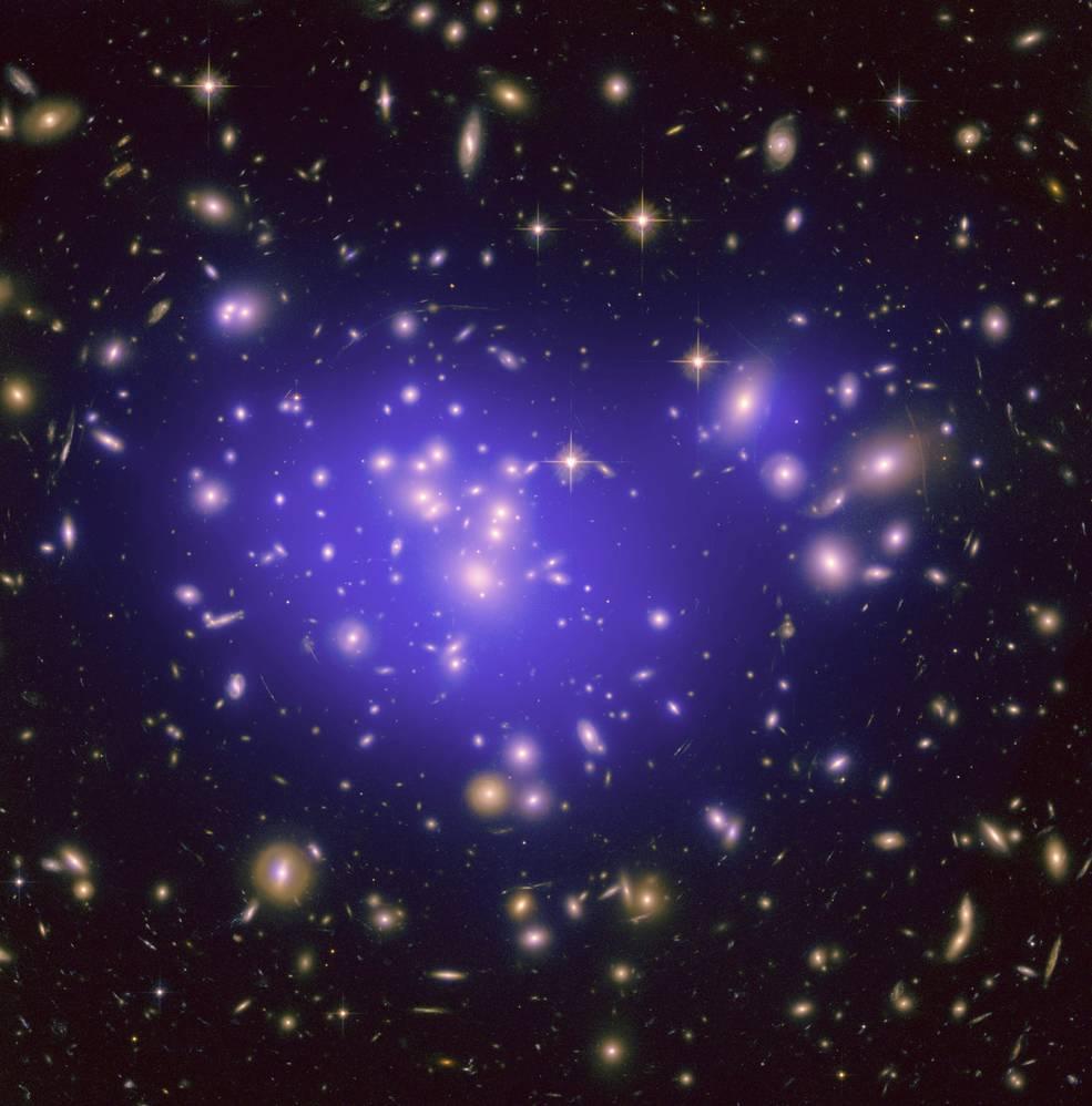 Zone centrale de l'amas de galaxies Abell 1689. Des centaines de galaxies apparaissent en couleur jaune sur fonds noir avec au centre de l'image un halo violet.