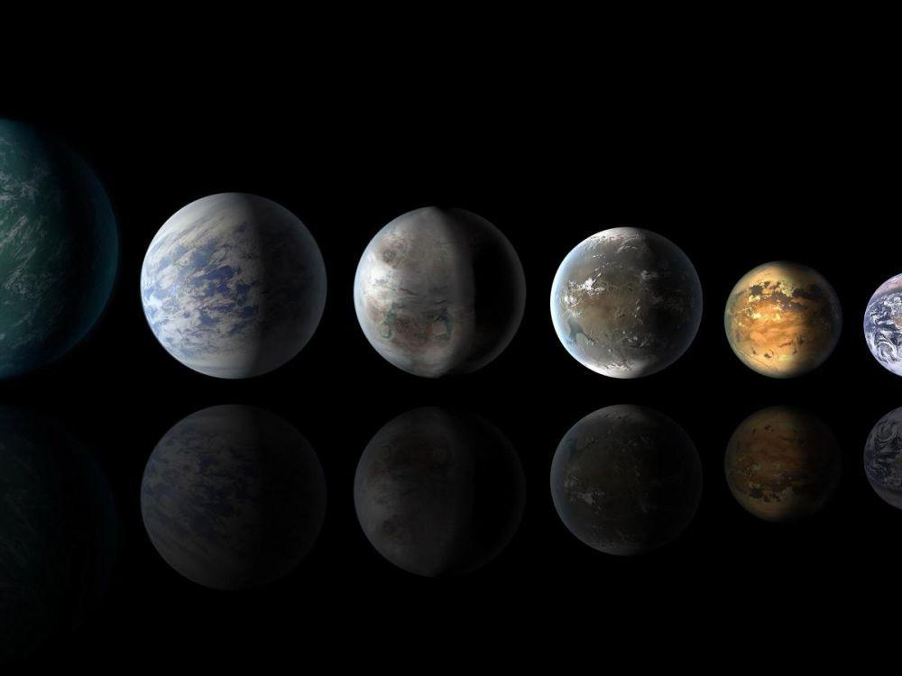 Vue d'artiste de quatre exoplanètes aux couleurs différentes qui semblent être riches en eau.