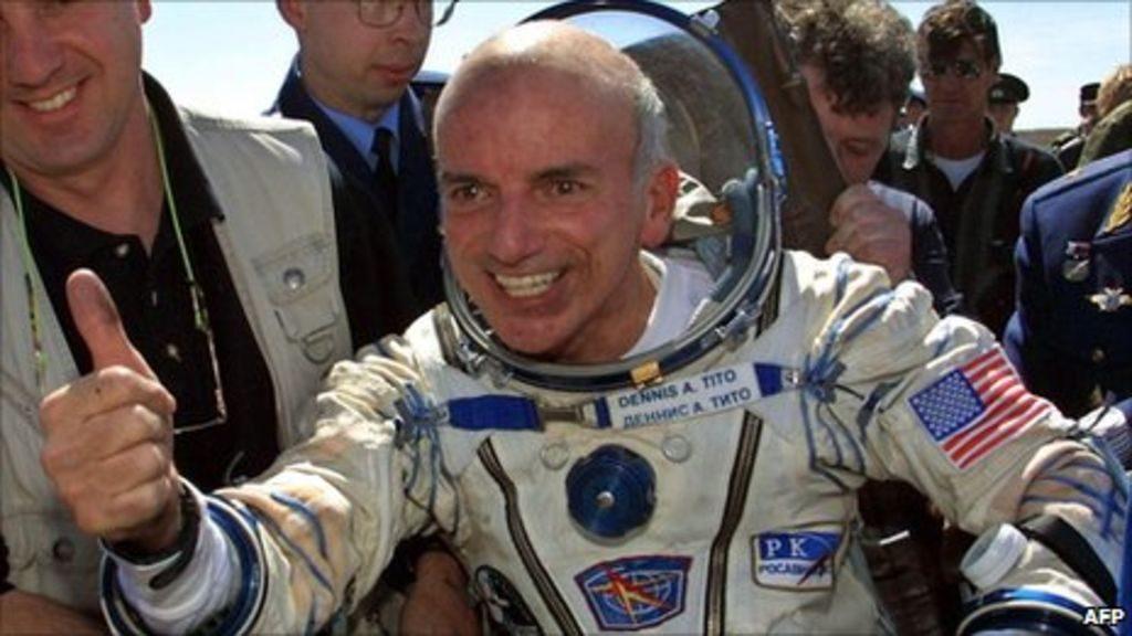 Dennis Tito, le premier touriste spatial à son retour en 2001, habillé de sa combinaison spatiale, un grand sourire et pouce levé.