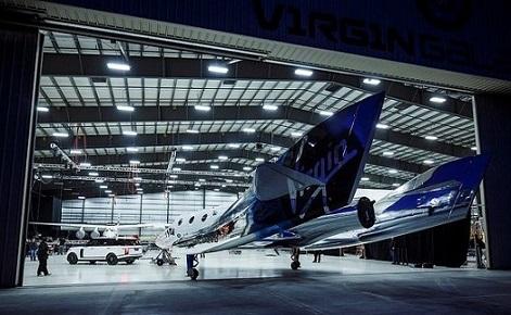 Le vaisseau spatial de Virgin Galactic dans un grand hangar, de nuit.