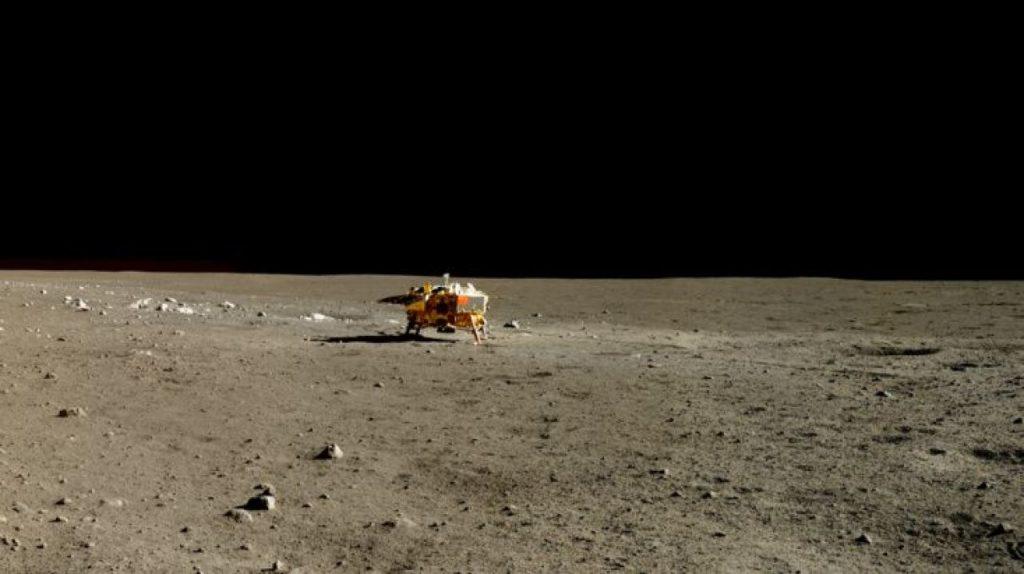Photo réelle de l'atterrisseur Chang'e 3 prise par le rover Yutu. On le voit petit, perdu dans l'immensité lunaire.