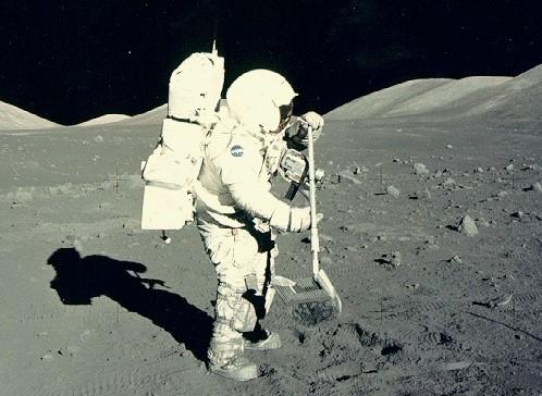 Photo de Harrison Schmitt en combinaison spatiale, au Soleil, qui ramasse des échantillons lunaires en 1972 (mission Apollo 17).