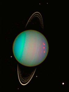 Uranus vue par Hubble : on voit la planète en couleurs bleu et violet, entourée de quelques-uns de ses satellites et de ses anneaux étroits représentés en blanc.
