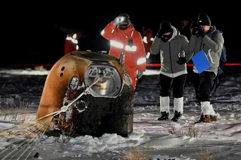 Photo de la sonde Chang'e 5 après son retour sur Terre. On la voit dans la neige, la nuit, capsule brûlée de couleur marron, entourée de trois scientifiques et ingénieurs habillés chaudement.