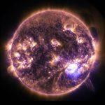 Éruptions solaires vues en UV lointain en décembre 2014 : on voit le Soleil en totalité, en couleurs orange et violet, avec plusieurs éruptions solaires de part et d'autre de la sphère en couleur jaune vif.