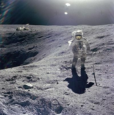 Charles Duke face à l'appareil photo en train de ramasser des échantillons à côté du cratère Plum. Un rover en fond.