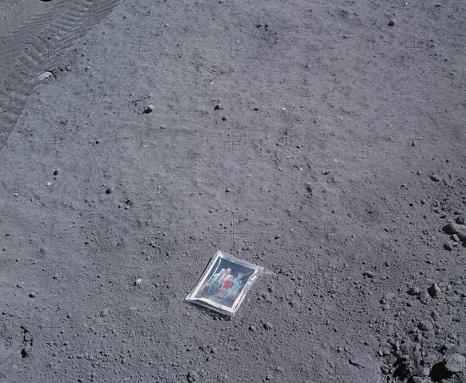Sol lunaire avec au centre de l'image la photographie que Charles Duke a déposée de sa famille sur le sol lunaire.