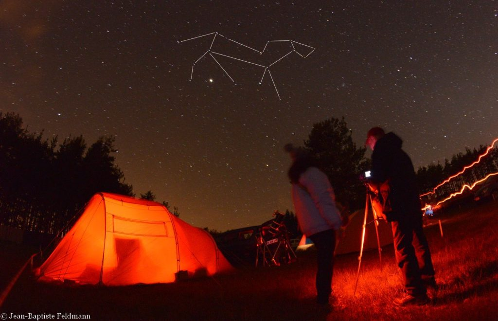 Photo of amateur astronomers observing the starry sky, with the constellation Leo and Jupiter looking like a bright speck of light just above their heads.