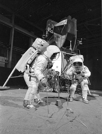 Photo en noir et blanc d'Armstrong et Aldrin en combinaisons lunaires qui s'entraînent à la récolte d'échantillons le 22 avril 1969.