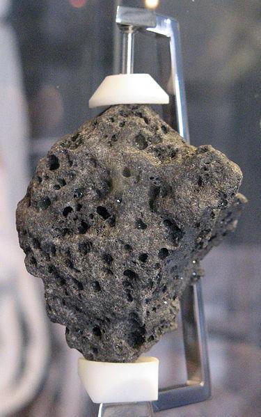 Photo couleur d'un échantillon de roche lunaire, qui semble volcanique car pourvue de trous, ramené par la mission Apollo 11.