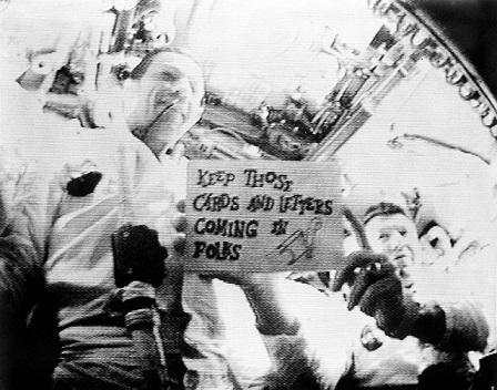 """Capture d'écran en noir et blanc de la première diffusion télévisée depuis l'espace dans laquelle les astronautes d'Apollo 7 brandissent un panneau indiquant """"Continuez à nous envoyer des cartes et des messages""""."""