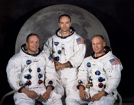 Photo couleur de l'équipage d'Apollo 11, de gauche à droite : Armstrong, Collins et Aldrin. Ils sont habillés de leurs combinaisons spatiales, sans scaphandre.