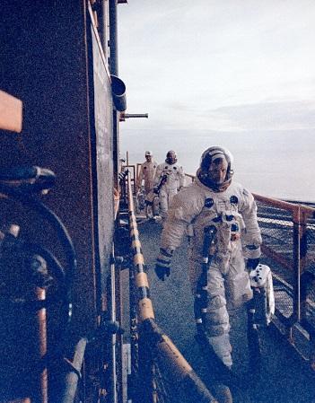 Photo couleur de Neil Armstrong qui mène son équipage jusqu'à la fusée, réserve d'oxygène à la main.