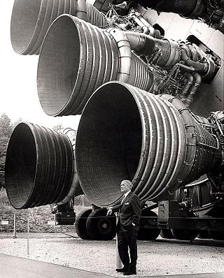Photo noir et blanc des moteurs F-1 du premier étage dominent leur créateur, Wernher von Braun.