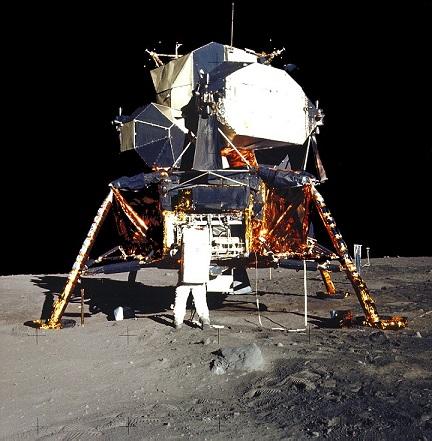 Photo couleur du module lunaire posé sur la Lune avec Buzz Aldrin qui y prend des instruments expérimentaux.
