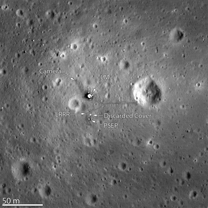Photo en noir et blanc de la vue de dessus du site d'atterrissage. On y voit le module lunaire et plusieurs instruments.