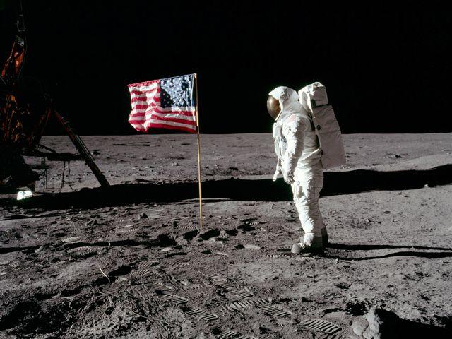Photo couleur de Neil Armstrong en combinaison spatiale, à la surface de la Lune, à côté du drapeau américain planté dans le sol.