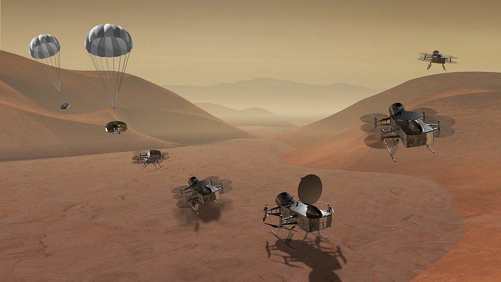 Vue d'artiste de la mission Dragonfly sur laquelle on voit un concept de robot volant autonome à six hélices horizontales, trois de chaque côté d'une structure en parallélépipède.
