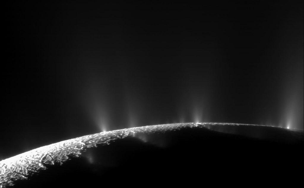 Photo en noir et blanc de la surface d'Encelade, trois geysers gris visibles à l'horizon.