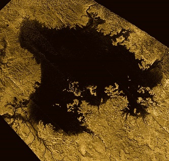 """Photo de Cassini d'un lac d'hydrocarbures à la surface de Titan. Le lac est noir autour de """"terres"""" en couleur jaune."""