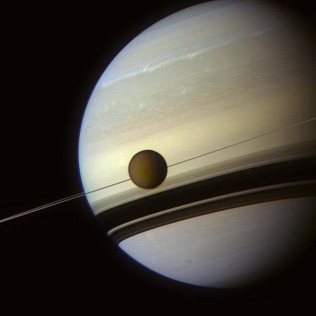 Photo de Saturne par Cassini où l'on voit les anneaux qui ne forment qu'une simple ligne vus par la tranche. Titan est également sur l'image, au même niveau que les anneaux.