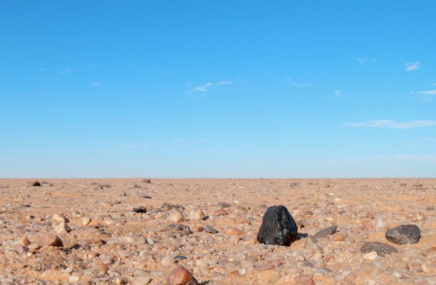 Météorite sombre sur le sol jaune pâle du désert du Soudan, sur fond de ciel bleu sans nuage.
