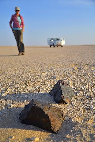 Illustration de la chasse aux météorites : deux météorites sont posées au premier plan sur le sol jaune du désert du Dhofar (Oman), derrière en flou une femme s'approche, elle est descendue d'un 4x4 aux portes ouvertes au troisième plan, aussi flou.