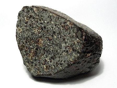 Météorite de type chondrite, exposée sur fond blanc. Elle est gris foncé avec des petits points en différentes nuances de gris, les chondrules.