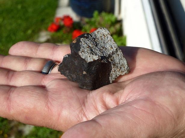 Météorite de couleur noir dans la main d'un chasseur de météorites. Le noir indique que sa chute est récente.