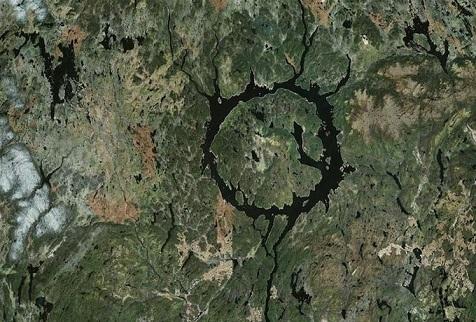 Vue du ciel d'un des plus grands cratères du monde, le Manicouagan : on voit un anneau d'eau en bleu marine qui en dessine ses extrémités car il a été rempli par un lac artificiel.