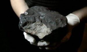 Photo de la plus grosse météorite de France découverte en 2018. Le gros caillou gris anthracite est tenu dans les mains gantées d'un membre du Muséum national d'histoire naturelle de Paris.