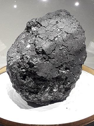 Photo de la météorite d'Orgueil, sur un support blanc, elle est ovoïdale et gris anthracite.