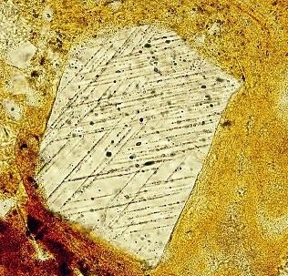 Quartz choqué entouré de verre naturel, vu en couleur jaune au microscope. Le quartz choqué est plus clair et parsemé de stries.