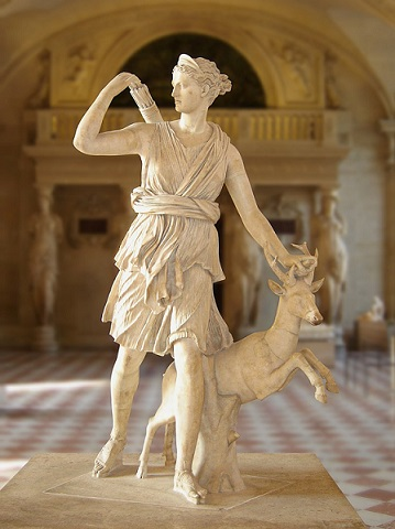 Dans un couloir du musée du Louvre, statue de la déesse Artemis en train de marcher, sa main gauche sur une biche et sa main droite prenant une flèche de son carquois.