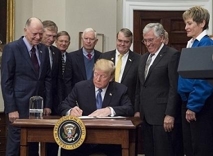 Donald Trump assis à un bureau en train de signer la nouvelle politique spatiale américaine en 2017, entouré par notamment des représentants du Congrès et les astronautes Jack Schmitt et Peggy Whitson.