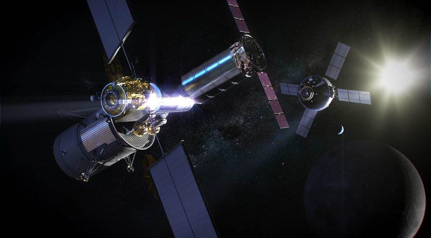 Sur fond noir avec la Lune en bas à droite de l'image, on voit une vue d'artiste du Gateway (à gauche) et du vaisseau Orion (à droite) en arrière-plan. Les deux sont en couleurs gris métallisé et possèdent des panneaux solaires.