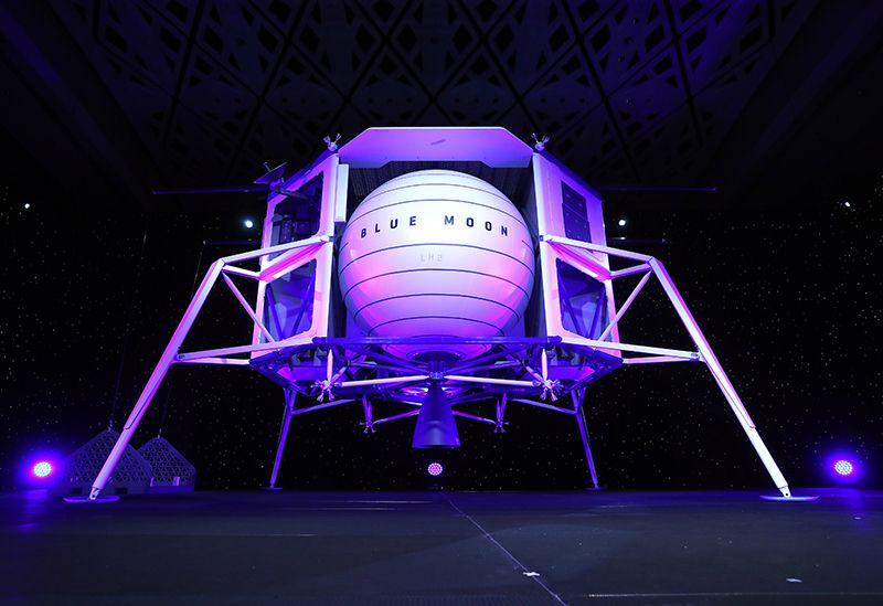 Sur une estrade, de couleur blanche et éclairé par des lumières bleu-violet, le concept d'atterrisseur lunaire de Blue Origin avec une sphère en son centre.