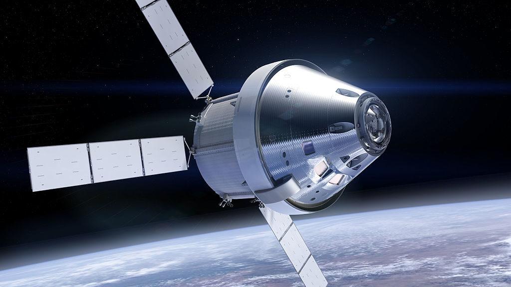 Dans l'espace avec la Terre en fond, on voit le vaisseau Orion, sa coiffe conique vers l'avant illuminée par le soleil. Toute la capsule est en couleur gris métallisé.